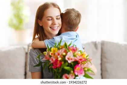 Der liebende kleine Sohn, der glückliche Mutter umarmt und während der Feierlichkeiten zu Hause mit dem Strauß der Alstroemerias Gruß begrüßt