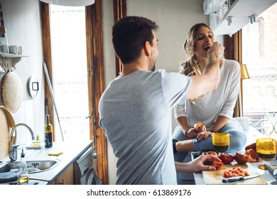 Loving man feeding woman while cooking dinner at kitchen.