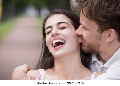 Loving man tickling and embracing laughing woman outdoors in park, tender boyfriend kissing or biting attractive girlfriend ear, telling funny news, story, family having fun together, close up