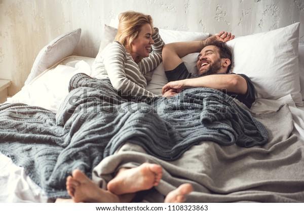愛する男女が寮で怠け者の時を楽しんでいる。彼らは毛布の下に横になって笑っている。幸せな女性は、配偶者がお互いの目を見つめている間、パートナーの手に触れる
