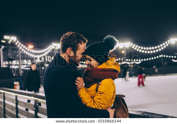Loving man and woman on the skating rink smiling at each other with their eyes closed