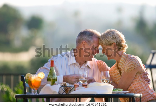 Loving mature couple eating at outdoor restaurant table