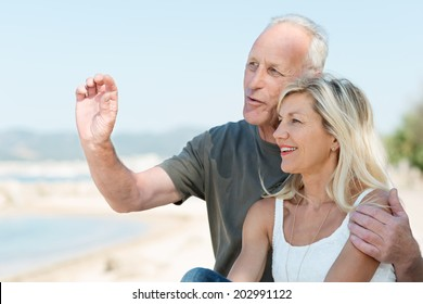 Loving mature couple enjoying a day at the sea standing in a close embrace overlooking the ocean having an animated discussion and gesturing