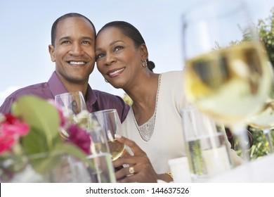 Loving middle aged couple celebrating with white wine outdoors