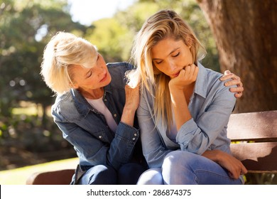 loving middle aged woman comforting her sad daughter at the park
