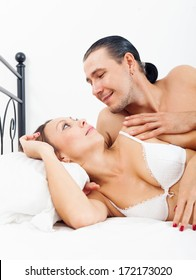 Loving middle-aged couple awaking together in bed