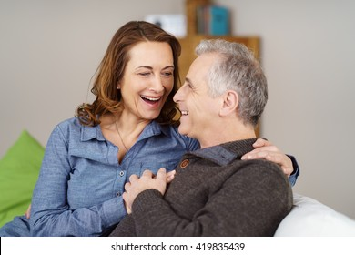 Loving middle-aged couple laughing together as they relax on a sofa at home in an intimate embrace