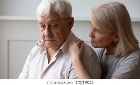 Loving middle-aged wife hug comfort sad distressed elderly 80s husband feeling loneliness, caring mature woman embrace caress support upset senior 70s man, suffer from depression or solitude