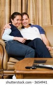 loving mixed race couple smiling sitting on a sofa in living room inside house
