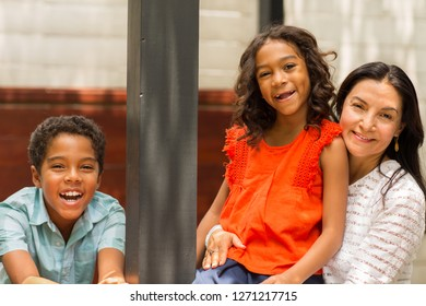 Loving mixed race family smiling outside.