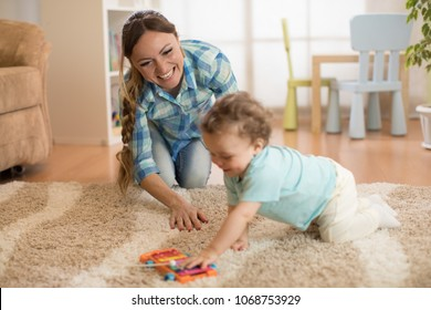 Loving mom and baby toddler playing and having fun time together at home.