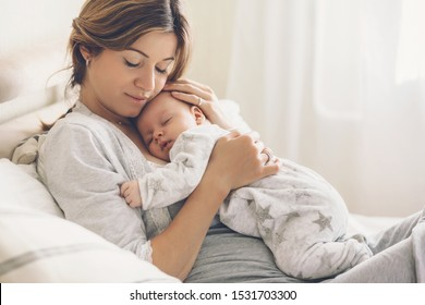 Loving mom carying of her newborn baby at home. Bright portrait of happy mum holding sleeping infant child on hands. Mother hugging her little 2 months old son.