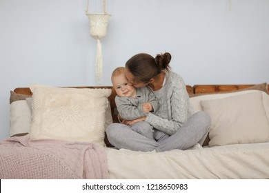loving mom hugs a charming baby 10 months old in a gray knit sweater, motherhood in a real interior and lifestyle