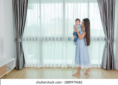 Loving mom laughing caressing touching noses with cute baby sitting on a sofa at home, happy mother and little child boy hugging having fun playing enjoy funny moments good time together.