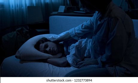 Loving mom looking at her sleeping son at night time feeling nostalgic, family