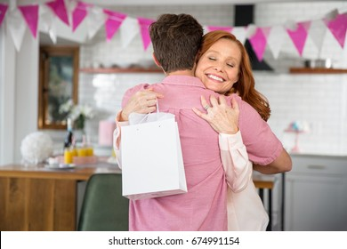Loving mother accepts a gift from a friend or family for her retirement party or birthday