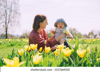 Loving mother and baby girl among yellow tulips flowers. Woman with her daughter playing outdoors in spring park. Family on nature. Image of Mother's Day, Easter. Tulip field in Arboretum, Slovenia.