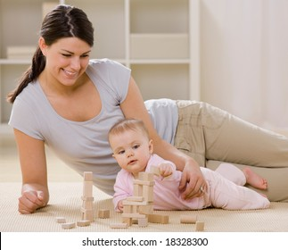 Loving mother and baby playing with wooden blocks on livingroom floor