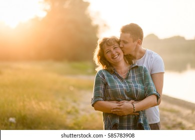 Loving mother being kissed by her adult son as he hugs her from behind