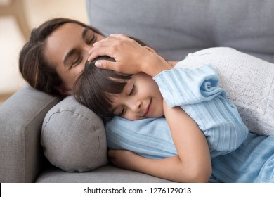 Loving mother caressing cute little daughter lying on sofa together, caring mom embracing kid relaxing enjoying nap, happy mum stroking hugging preschool girl cuddling resting on comfortable couch