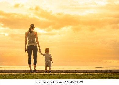 Loving mother and child walking together by the sea holding hands.