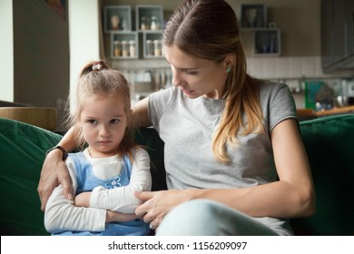 Loving mother consoling or trying make peace with insulted upset stubborn kid daughter avoiding talk, sad sulky resentful girl pouting ignoring caring mom embracing showing support to offended child