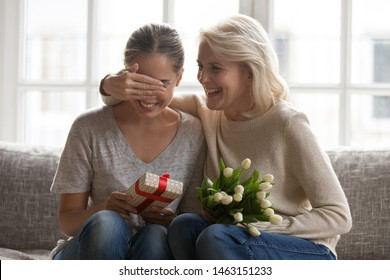 Loving mother cover eyes with hand of grown up daughter prepare for her gift and spring flowers, family sit on couch at home celebrating birthday, life event, showing love attention and care concept