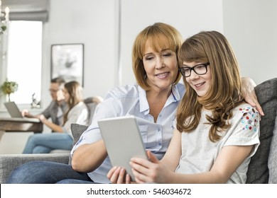 Loving mother and daughter using tablet PC with family sitting in background at home