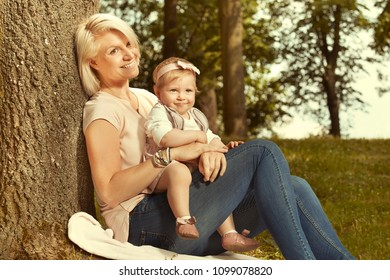 Loving mother enjoying sunny afternoon in park with her daughter