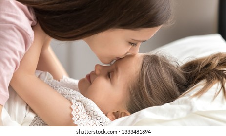 Loving mother gently kissing cute kid daughter wishing good night sweet dreams or waking up early, caring mom embracing little child girl lying in bed awaking enjoying happy family warm morning