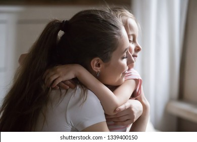 Loving mother give strong hug to daughter with eyes closed. Happy mommy and baby feel relaxed, enjoy spend time together. Mom calm down little girl. Family relationship, interaction, support concept