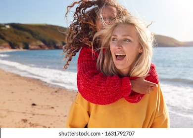 Loving Mother Giving Daughter Piggyback As They Walk Along Winter Beach Together