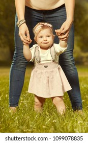 Loving mother guiding in park her daughter to make first steps