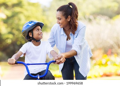 loving mother help her cute son ride a bicycle