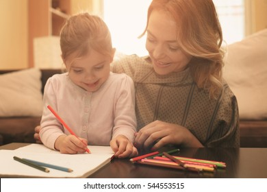 Loving mother helping her daughter drawing.