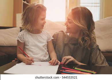 Loving mother helping her daughter write a letter. Looking at each other.