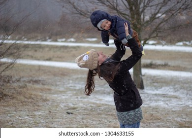 loving mother holding her beautiful little adorable babyboy up with snowy nature in the background