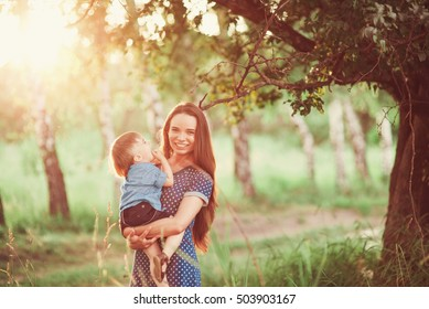 Loving mother holding son in her arms, plays with him and hugs him. Family rest on the nature. soft focus