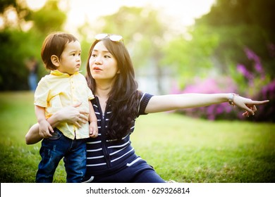 Loving mother holding son in her arms, plays with him and hugs him. Family rest on the park.