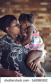 Loving mother kissing her baby girl rural african real people