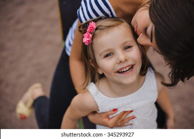 Loving mother kissing her daughter in park