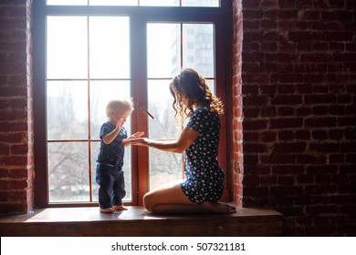 Loving mother playing with her baby sitting on a window