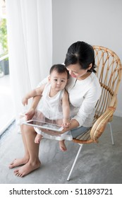 Loving mother playing with her baby sitting on chair near  window