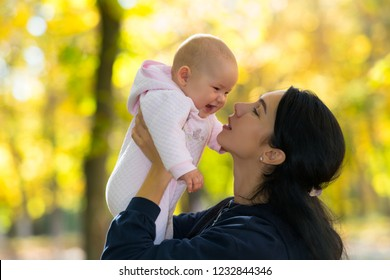 A loving mother playing with her happy, laughing baby in a park scene with beautiful, bright autumn light.