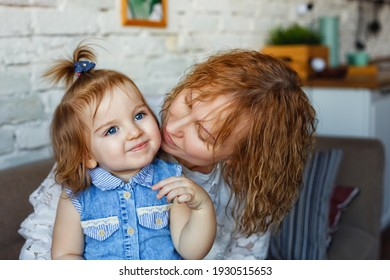 A loving mother plays with her child. Mother and daughter sit on the wooden floor near a large window.