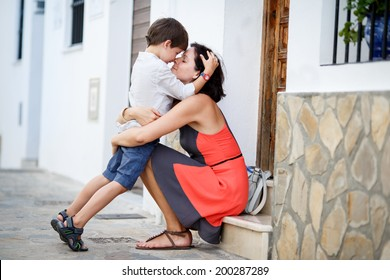 Loving mother and son hugging outdoors on beautiful summer day