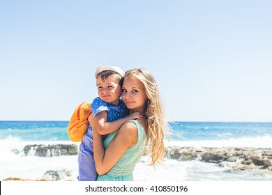 Loving mother and son hugging outdoors on beautiful summer day.