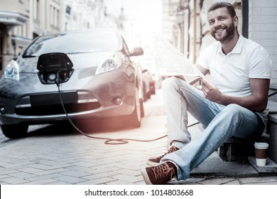 Loving my life to the fullest. Radiant young gentleman in casual smiling cheerfully while sitting outdoors and waiting for his eco friendly electric automobile charging in the background.