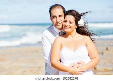 loving newlywed couple on beach