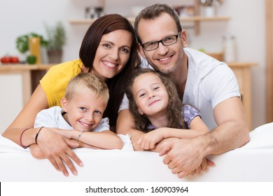 Loving parents with their little son and daughter posing together for a portrait leaning over the back of a large sofa in the living room